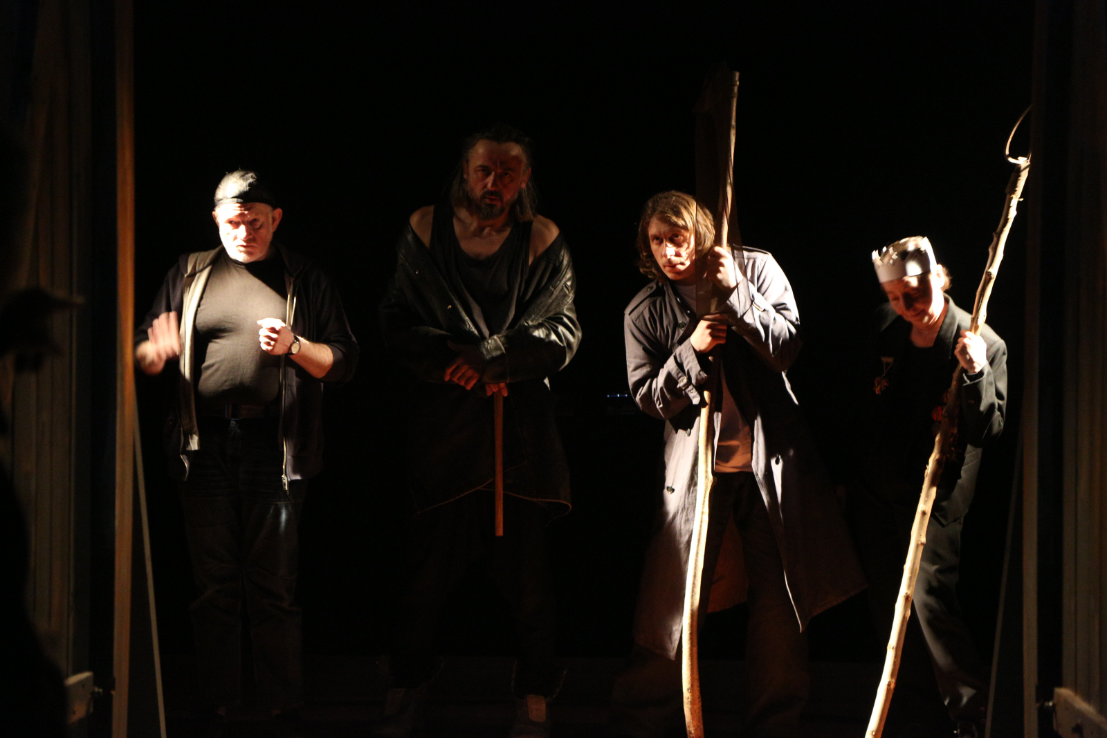 Czterech mężczyzn stoi w półmroku. Dwóch podpiera się na drewnianych laskach