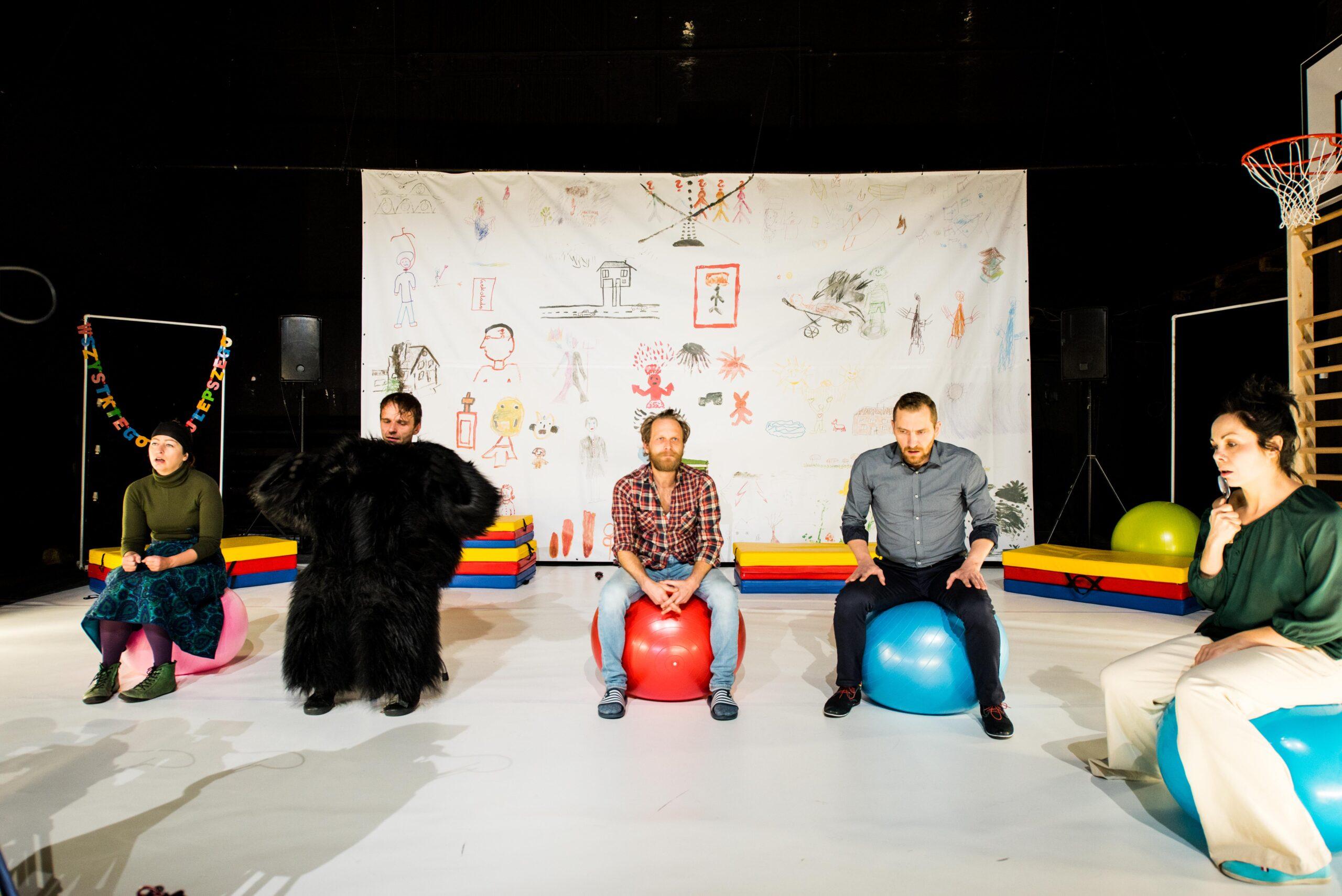 Grupa 5 osób siedzi na dmuchanych piłkach. Za ich plecami znajdują się dziecięce rysunki