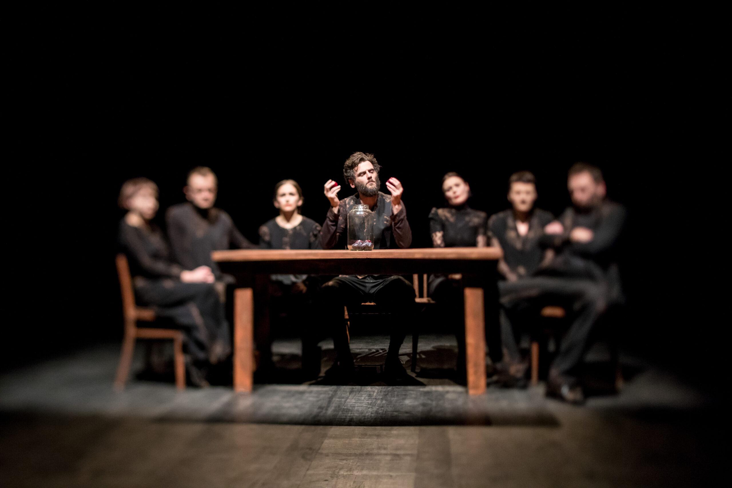 Fotografia przedstawia 7 osób w czerni siedzących przy stole. Centralna osoba jest wyraźna, pozostałe są rozmazane