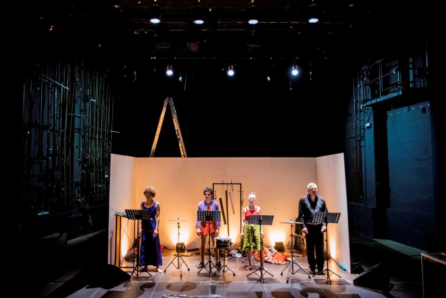 Czwórka muzyków stoi w przed pustymi partyturami w białym pomieszczeniu, które znajduje się w magazynie
