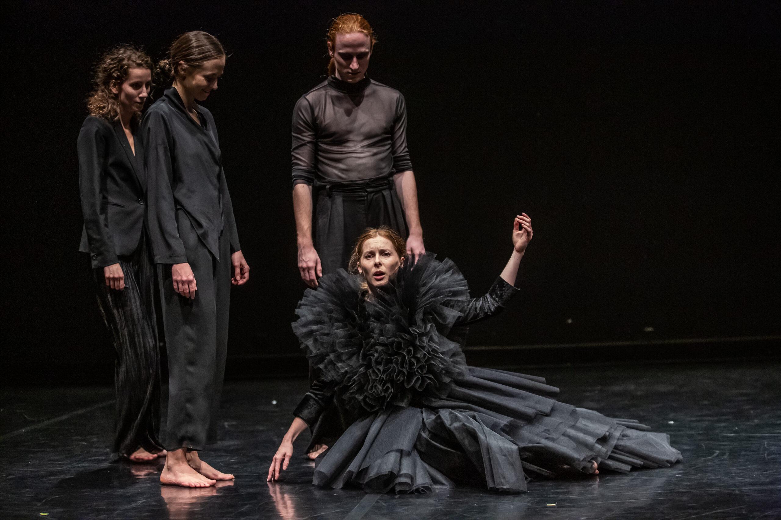 Trzy osoby w czerni stoją nad kobietą w czarnej sukni