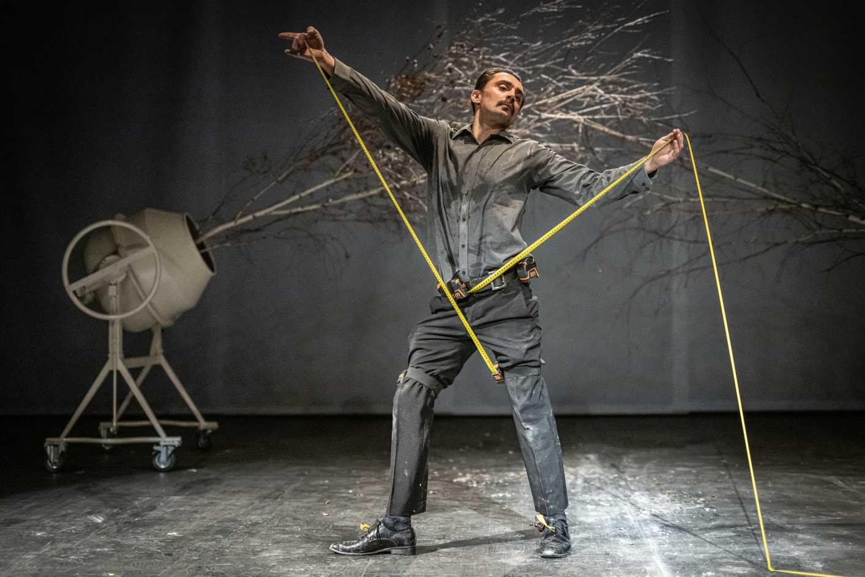 Mężczyzna w garniturze mocuje się miarkami. Za nim znajduje się biała betoniarka z drzewem