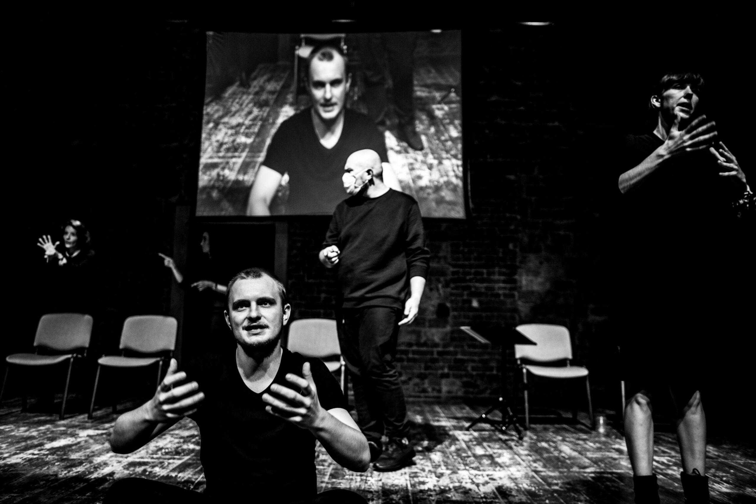 Czarnobiała fotografia przedstawia 4 osoby. Jedna osoba siedzi gestykulując, za nią znajduje się mężczyzna w maseczce. Po prawej i po lewej kobiety tłumaczą w języku migowym